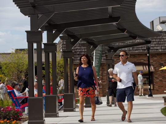 Joel and Wendy Thompson of Port Huron enjoy wine under the pergolas at the Riverview Plaza courtyard Thursday.
