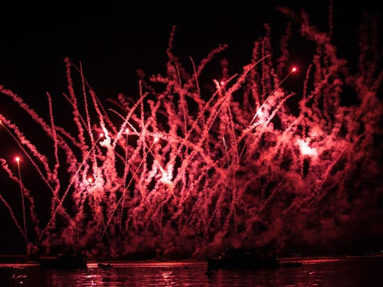 Fireworks illuminate the surface of the water.