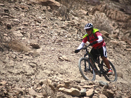 Carlos Godinez bikes down the Mike Schuler trail Monday in Palm Desert. A man died Saturday while hiking the adjacent Bump and Grind trail.