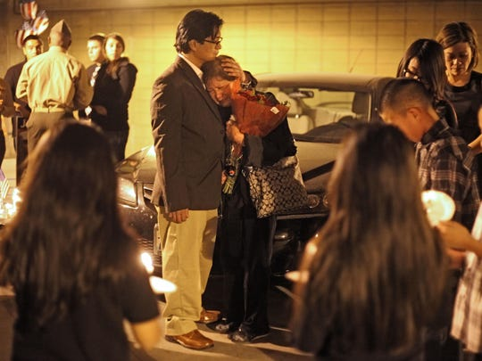 Richard Lui/The Desert Sun Marine Cpl. Allan DeVillena II's father, Allan DeVillena Sr., comforts his grandmother, Victoria DeVillena, during a candlelight vigil for the Marine, who was fatally shot by Palm Springs Police on Nov. 10, 2012. The vigil was held five days later, at the garage where the shooting took place. Photo taken on Thursday, November 15, 2012.(Richard Lui The Desert Sun)