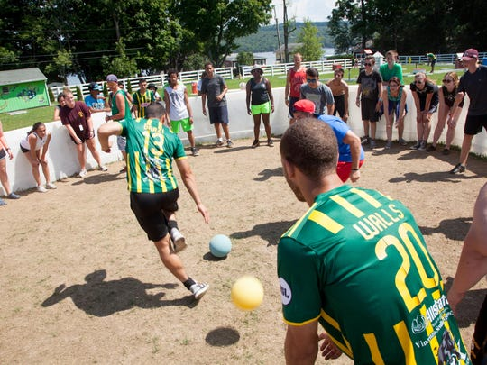 Rhinos midfielders Mike Garzi, center, and Tony Walls (20) play a game with campers at Camp Good Days and Special Times.
