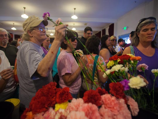 Mourners at the a vigil for Lara Sobel take flowers at the Old Union Hall in Barre to carry on a march through downtown.