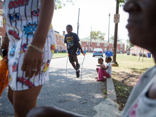 Kids play outside near where a 10-year-old boy was shot in the head in the 700 block of Townsend Place, a brick residential structure just west of South Heald Street in Wilmington.