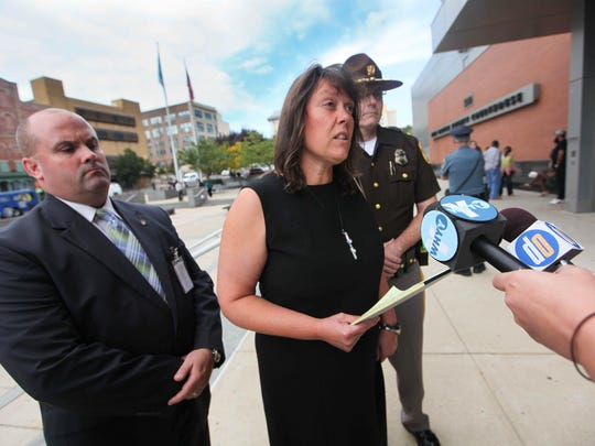 Kathy Szczerba reads a statement outside New Castle County Courthouse where David Salasky entered a plea of guilty but mentally ill in the 2011 fatal stabbing of her husband, New Castle County Police Lt. Joseph Szczerba, on Sept. 30, 2013.
