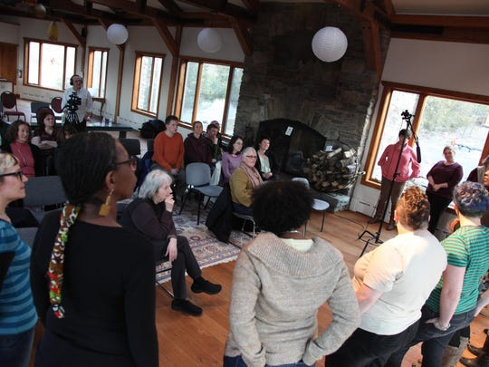 Attendees listen in during a 2013 TMI Project workshop at Lifebridge in Rosendale, Ulster County. Standing on the far left in blue stripes is TMI Project's editorial director, Sari Botton. On the right in the pink sweater is Eva Tenuto, the organization's executive director.