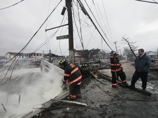 In this Oct. 30, 2012 photo, a firefighter hoses down burning embers from houses destroyed by a fire that raged during Superstorm Sandy along Fulton Walk in the Breezy Point neighborhood in the Queens borough of New York. Four years after the storm created a catastrophe on the coasts of New York and New Jersey, the coastline has come a long way toward recovery. But the catastrophic flooding also brought permanent changes to the shore. Some areas that have been rebuilt look dramatically different. (AP Photo/Mark Lennihan)