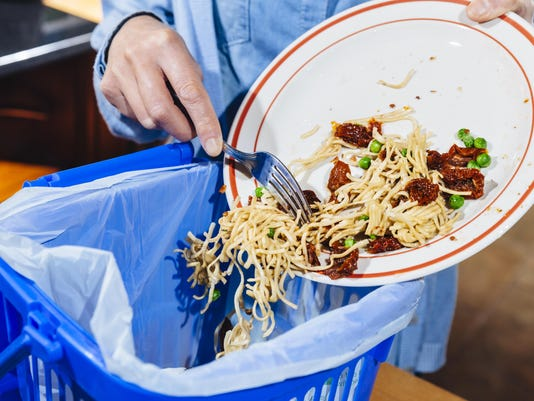 Woman scraping food leftovers into bin