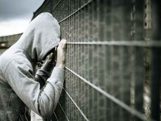 Lonely Man with Hood Leaning on a Fence