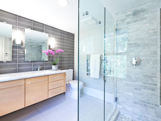 A contemporary modern bathroom design with glass enclosed shower stall with marble tiles, vanity and double sink counter.