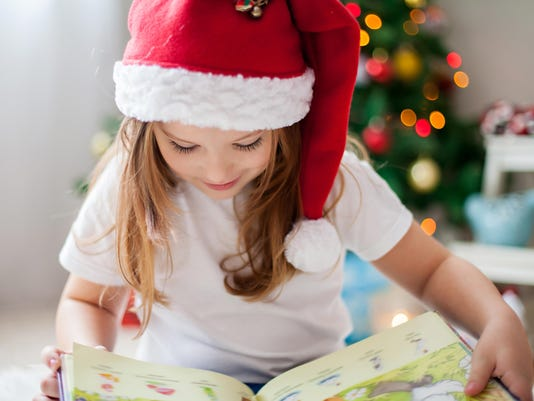 Beautiful girl, reading a book in front of Christmas tree