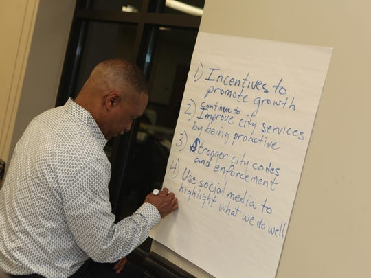 Springfield Electric's Director Robert Gardner writes down ideas for his group during the city's strategic planning meeting.