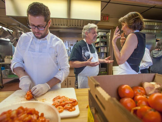 From left, Jesse LeClair dices tomatoes while Joe Lemieux and Marianna Shadroui Boiven discuss final planning details at the Elk's Lodge in Barre.
