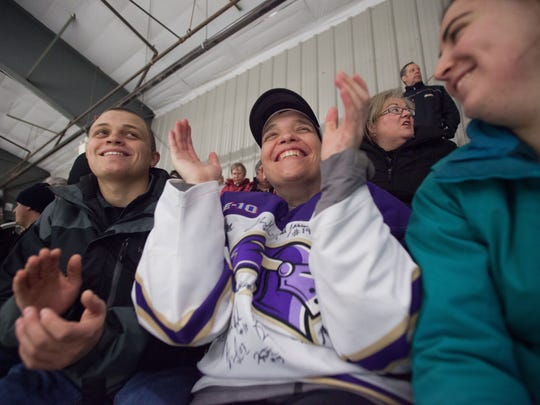 Justin Sell, left, Christian Sell, center, and Delaney Douglas watch the Norwich/Saint Michael's game on at Cairns Arena last week.
