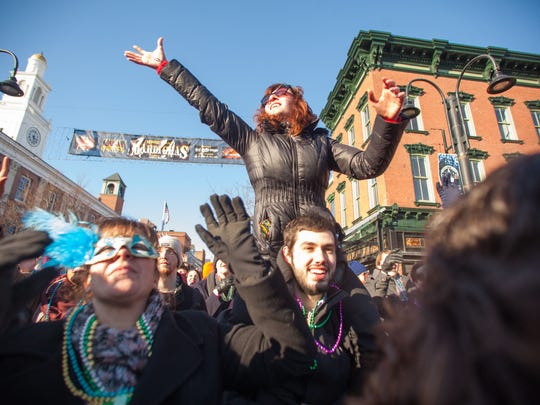 Brooke Saffren rides the shoulders of Dylan Welch as she competes for beads on Main Street in 2015.