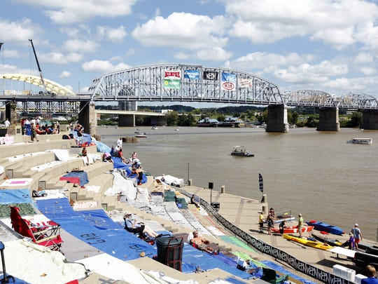 People mark their spots with tarps and blankets along the Serpentine Wall during Riverfest as they wait for the start of last year's WEBN fireworks.