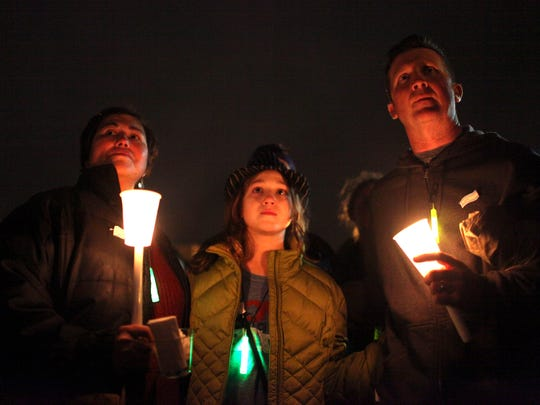 """Zay Crawford (center), a 12-year-old transgender girl from Yellow Springs, holds hands with her mother, Chasilee (left), and father, Jason (right) at a candlelight vigil to remember the life of Leelah Alcorn, a 17 year-old transgender girl, who committed suicide last month, in Kings Mills, Ohio. Saturday, January 3, 2015. Zay's grandparents and brother also attended the event to support. Chasilee said, """"We are a family. We love her for who she is and for what she is."""""""
