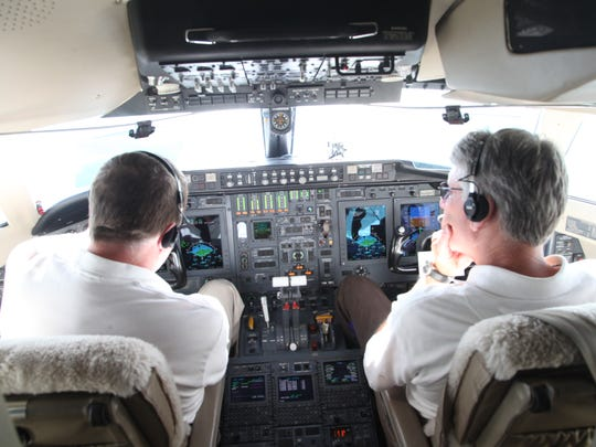 Rockwell Collins pilots Keith Kankelfitz, left, and Tom Yerke sit in the cockpit of a Bombardier Challenger 601 on a flight to demonstrate the company's weather radar.