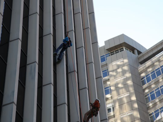 """Register Editor Amalie Nash makes her way down the Financial Center building as part of Special Olympics Iowa's annual """"Over the Edge"""" event."""