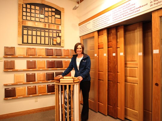 Jodi Gosse stands in a Drexel Building Supply showroom in Campbellsport that features doors and samples of interior finish.