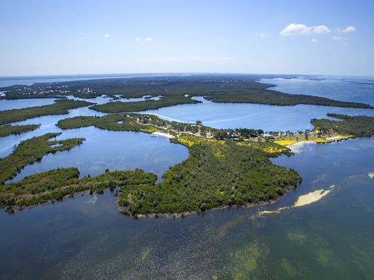 An aerial photograph shows Little Bokeelia Island off Pine Island. The island is listed at $24.5 million and includes a pool, pond and a 1920s mansion on 100 acres.