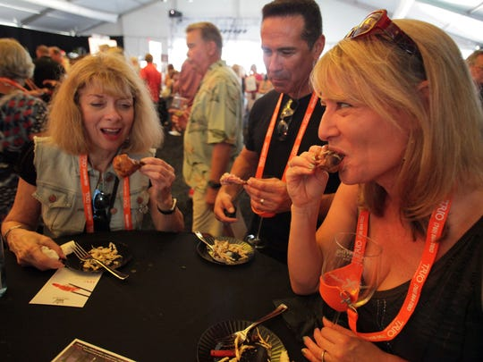(From the Left) Lorraine Brankline, of Palm Desert, Tom and Heather Flores from Yuccipa taste hickory smoked chicken osso bucco braised in BBQ sauce on a summer slaw by Babe's Bar-B-Que in Rancho Mirage served at the 4th annual Food + Wine Festival Palm Desert on Saturday, March 22, 2014.