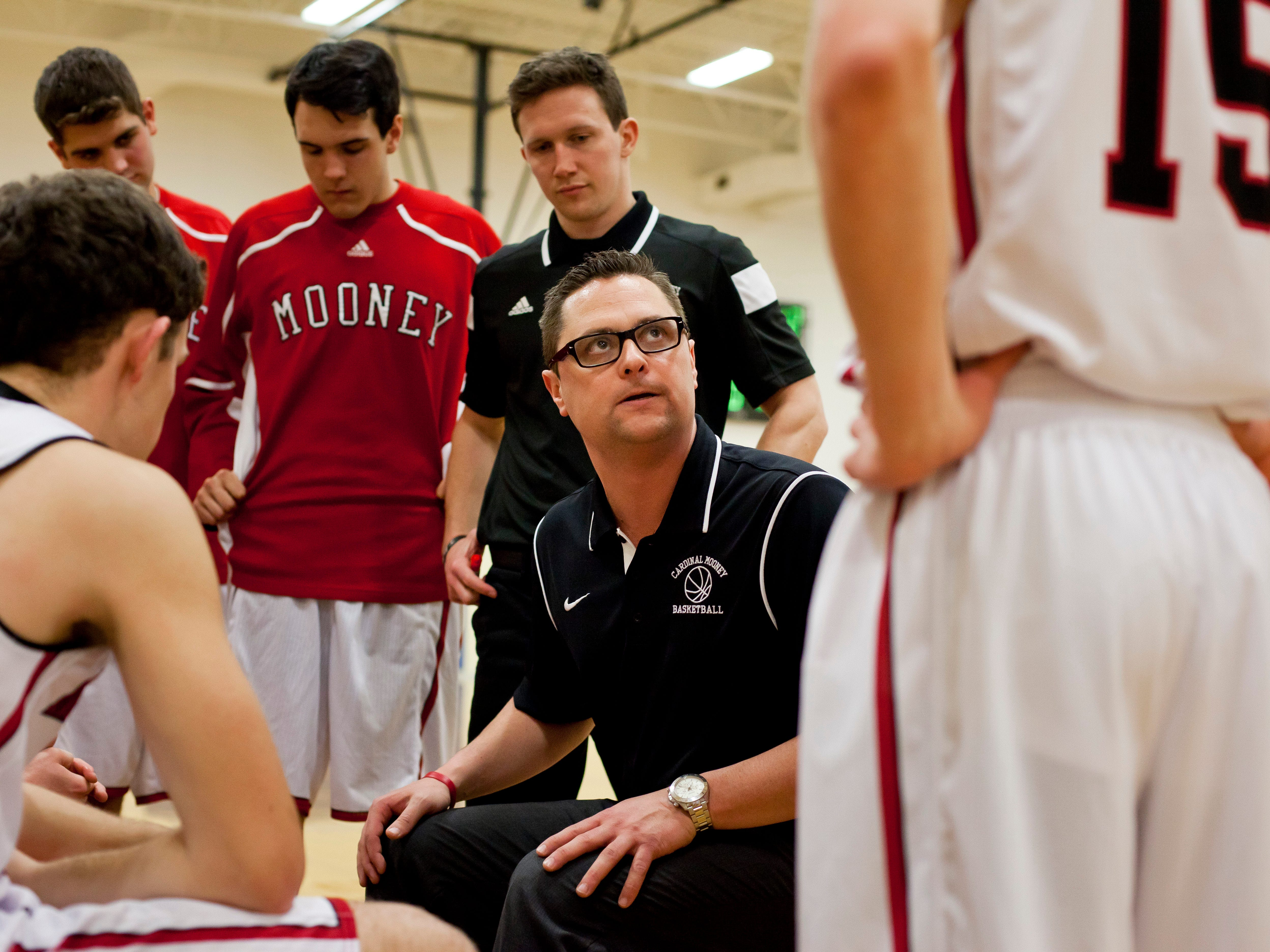 Cardinal Mooney coach Mike McAndrews talks with players in a time out during a basketball game Tuesday, Feb. 17, 2015 at Cardinal Mooney High School in Marine City.