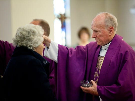 The Rev. Joe Gagnon places ashes on the forehead of parishioners during Ash Wednesday Mass at St. Joseph Catholic Church in Port Huron.