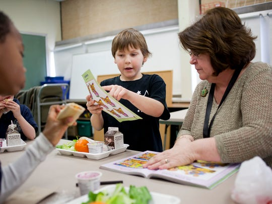 """Pam Dickinson, from Women's Life Insurance Society, plays a """"spot the difference"""" game with her lunch buddy Quinton Morgan, 9, Feb. 18, 2015 at Woodrow Wilson Elementary School in Port Huron. The Lunch Buddies program pairs up students with adults from the community."""