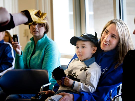 Courtney Sklba, of Port Huron, holds her son Boone Sklba, 3, as he reacts to being shown a bat Tuesday at the St. Clair County Administration Building in Port Huron.
