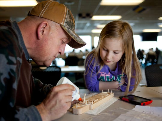 Haylee Haack, 8, watches as her grandfather, Tom Firmingham, of North Branch, helps her glue together a model boat Saturday, at the Great Lakes Maritime Center in Port Huron.