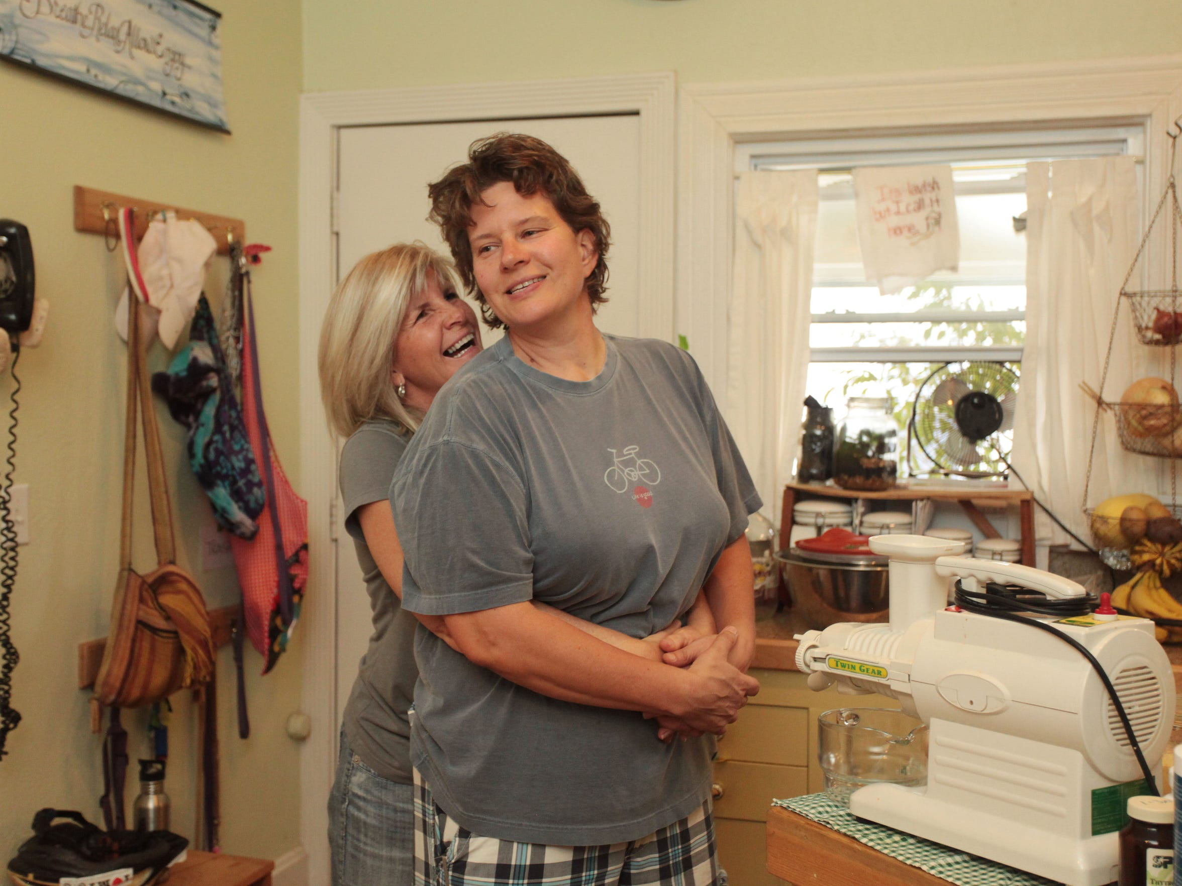 Mary embraces Sue in their kitchen as Sue makes shepherd's