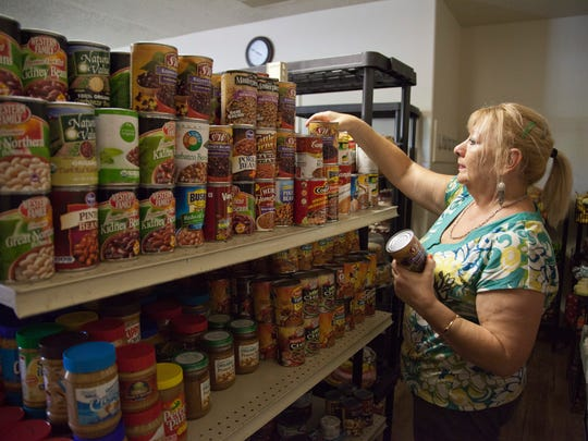 Fila Bukowiecki, who works for the community resource center, organizes food in the main pantry of the Switchpoint Poverty Resource Center Wednesday, Sept. 3, 2014.