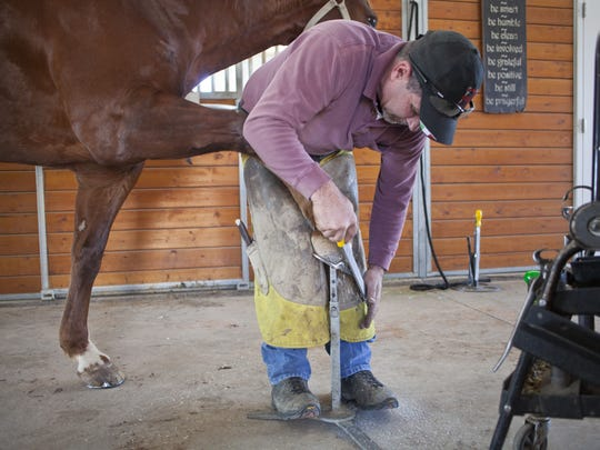 Wes Sharp, a certified journeyman farrier from Diamond Valley, finishes attaching a horseshoe to Ty, a Washington Fields horse, on Jan. 15.