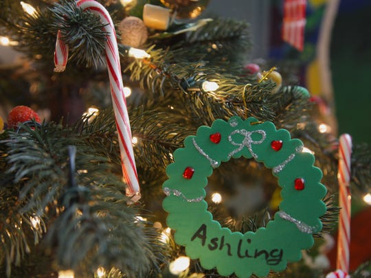 Wreaths hand-painted with resident children's names decorate the Christmas tree at Staunton's Valley Mission shelter, where Santa made a surprise visit Saturday. The Mission's fastest growing population is families with children.