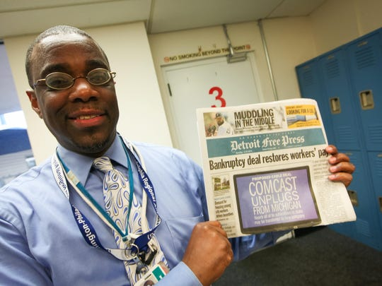 Airport director Stephen D. Williams holds a Detroit newspaper that someone brought on the first day of service from that city.