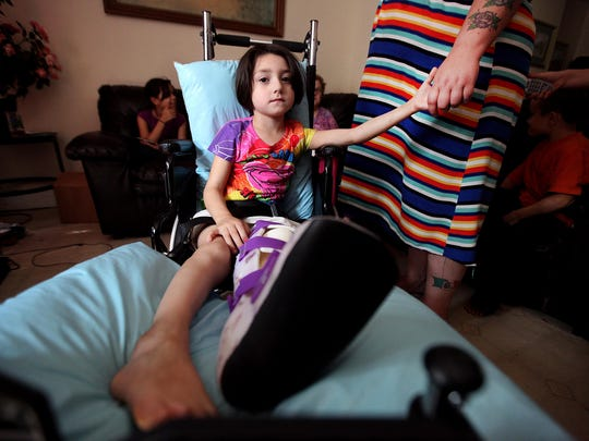 Golonda Grant holds her 5-year-old daughter Jazmine Galan Grant's hand as she sits in a wheelchair recovering from a gunshot wound to her left leg, Thursday, August 22, 2013.