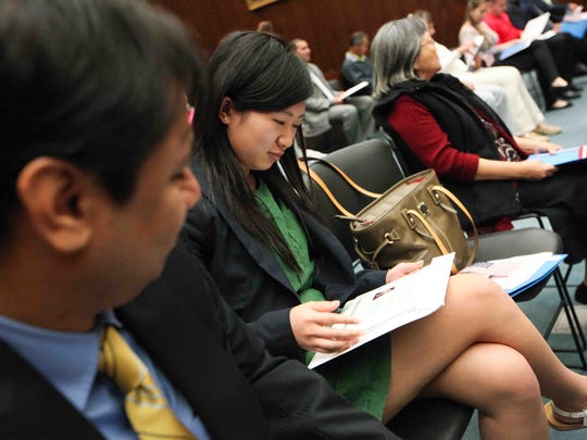 """Rong Ping Zhang (center), a University of Delaware senior who's majoring in international business, marketing and finance, looks at her U.S. citizenship certificate. Twenty-eight people from 18 different countries attended their naturalization ceremony at the J. Caleb Boggs Federal Building on Thursday, Oct. 2, 2014. Zhang emigrated with her family from China to Delaware when she was """"6 or 7."""""""