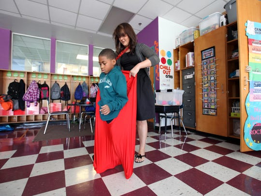 First grade teacher Emilie Bullins puts a therapy sock on 7-year-old Zaiequan Reid-Torres, a first grader at Stubbs Elementary Stubbs Elementary School, who was having a hard time controlling his feelings. The sock helps sooth children and bring them comfort.