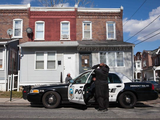 Cpl. Devon Jones checks to see if there are any outstanding warrants on a man in the area of East 24th Street in Wilmington.