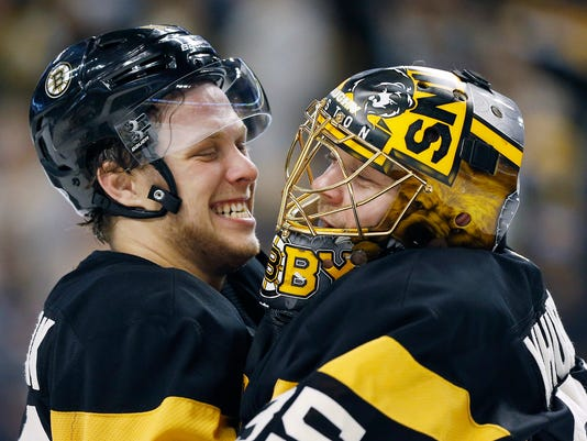 Boston Bruins' David Pastrnak, left, of the Czech Republic, celebrates with teammate Anton Khudobin (35), of Kazakhstan, after the Bruins defeated the New Jersey Devils in an NHL hockey game in Boston, Saturday, March 4, 2017. (AP Photo/Michael Dwyer)