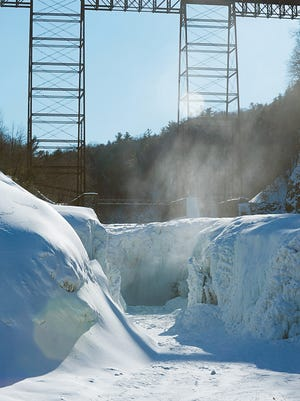 Mist rises above a mostly-frozen upper falls Monday, Feb. 23, 2015, at Letchworth State Park. Due to the deep freeze, the park's middle and upper falls  are almost entirely encased in stories-high layers of ice and snow.  (AP Photo/The Daily News, Rocco Laurienzo)