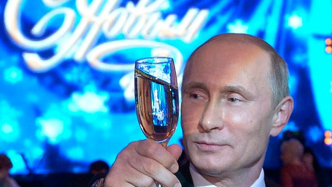 "File- Russian President Vladimir Putin, toasts during a New Year dinner in Khabarovsk, Russia's Far East, Tuesday, Dec. 31, 2013, with a neon sign behind declaring ""Happy New Year""."