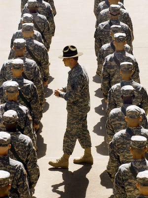 A drill sergeant keeps an eye on basic trainees as they go through formation training during their second week at Fort Sill, Okla., on April 10, 2006.