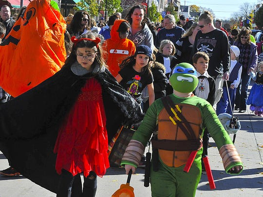 """A devilish young girl and a ninja turtle were among the many costumed children marching down Third Avenue in the Halloween Parade at last year's """"Thrills on Third"""" in downtrown Sturgeon Bay."""