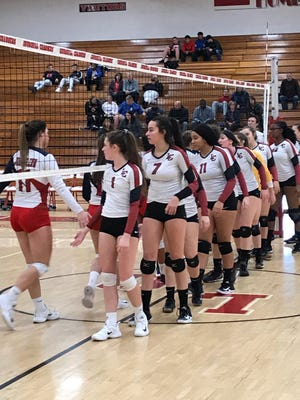 Livonia Churchill volleyball players Grace Vaeth (1), Annabelle Dunn (7) and teammates greet Westland John Glenn players such as Carley Loving (11) following Wednesday's district contest.