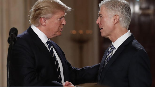 President Donald Trump shakes hands with Judge Neil Gorsuch in the East Room of the White House in Washington, D.C. on Tuesday after announcing Gorsuch as his nominee for the Supreme Court.