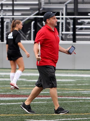 Ryan Puntiri coaches one of the girls on the soccer team during their practice at the high school on Friday, Aug. 25, 2017.