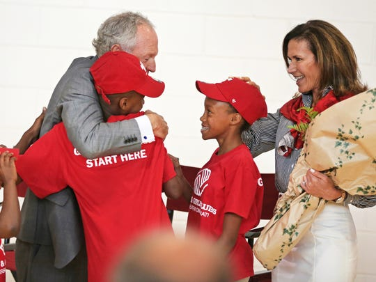 Larry and Rhonda Sheakley get hugs and flowers from some of the boys and girls during opening ceremonies for the Larry & Rhonda Sheakley Boys & Girls Club in Price Hill. The project was one of Major League Baseball's Legacy Projects for the All-Star Game. The new facility is 17,000 square feet.