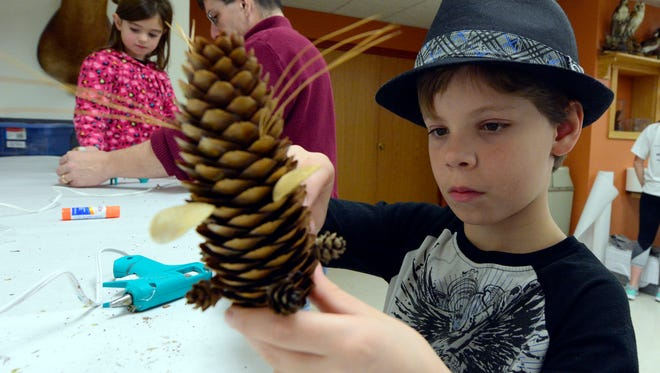 Owen Sitler, 10 of York, creates a holiday ornament out of natural items, at Richard M. Nixon County Park, Sunday Dec. 6, 2015. Visitors created all sorts of ornaments from materials like pine cones, nuts, and dried flowers. (John A. Pavoncello - The York Dispatch)
