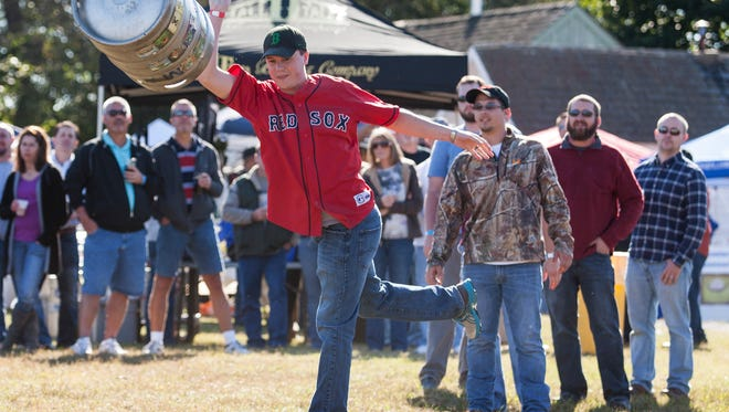 Jeremy Larlee, who's based at Dover Air Force Base, competes in the keg toss at last year's Delaware Wine and Beer Festival at the Delaware Agricultural Museum in Dover.